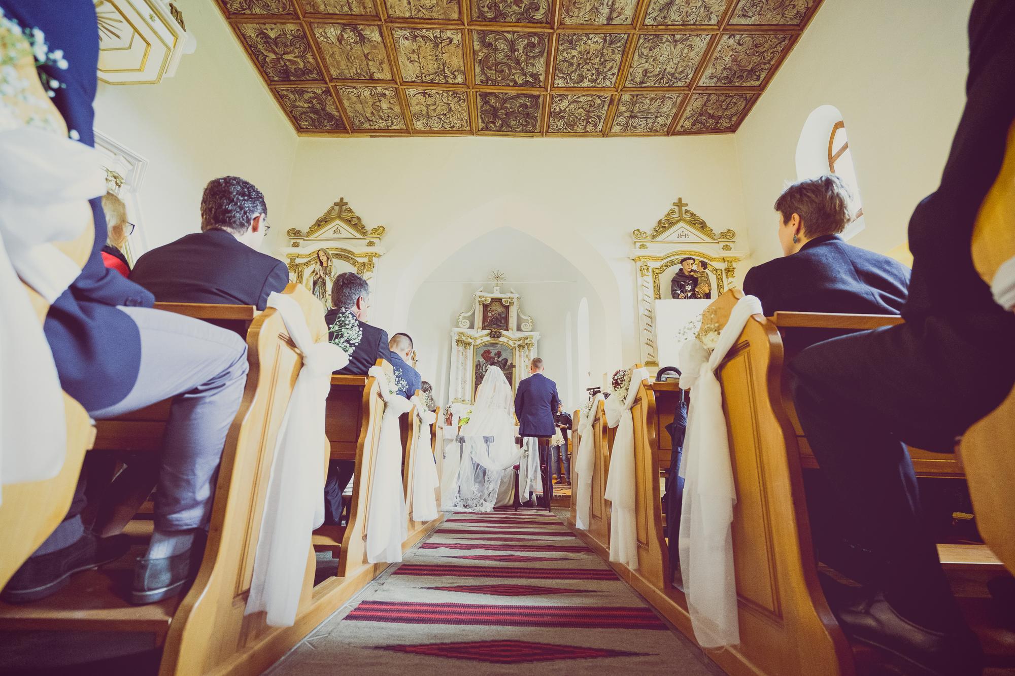 fotografie de nunta, cununie, miri in biserica, tavanul pictat, mirii din spate, cadru larg cu interiorul bisericii