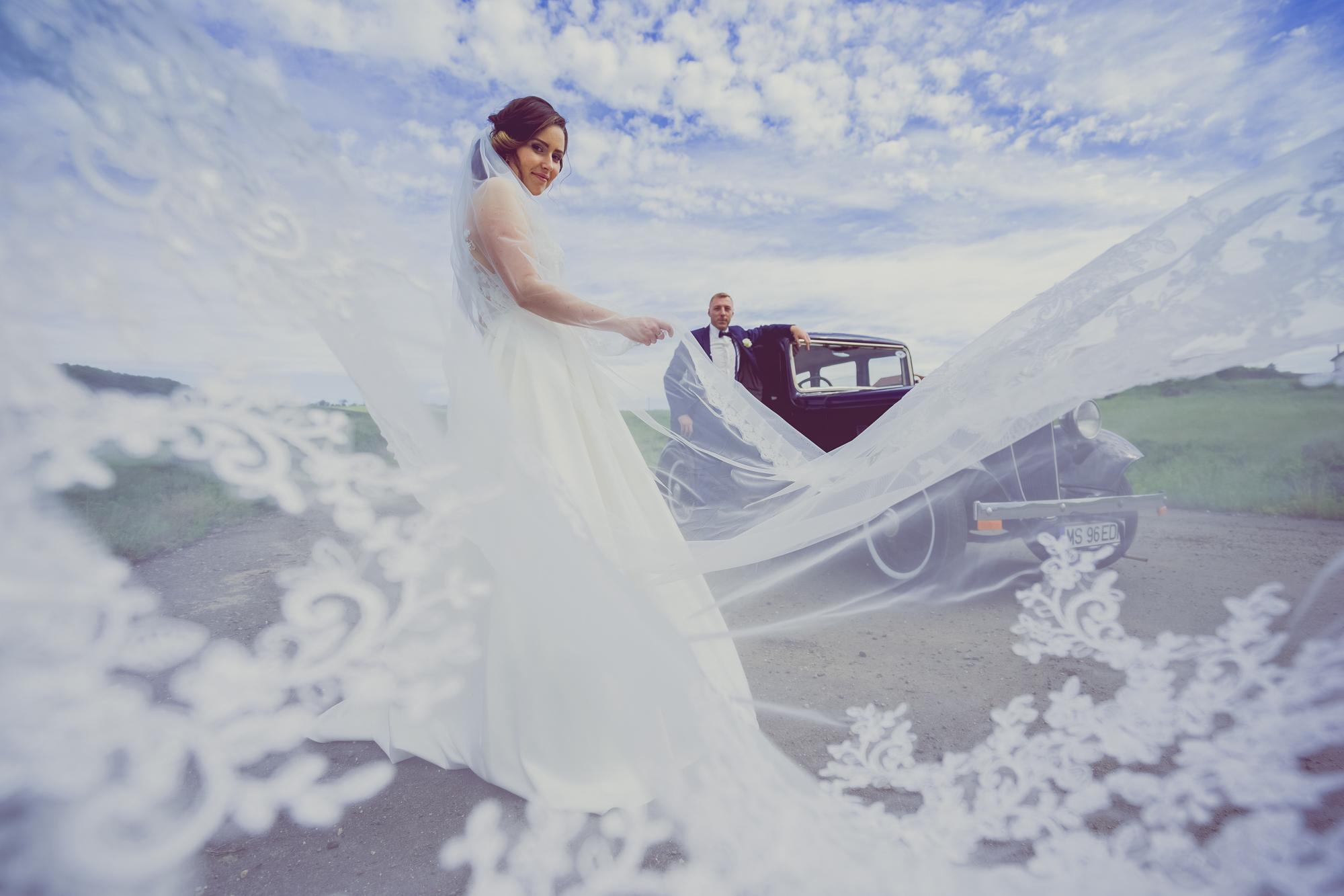 fotografie de nunta, mirii cu masina de epoca, cadru larg cu cer senin , voalul miresei zboara,