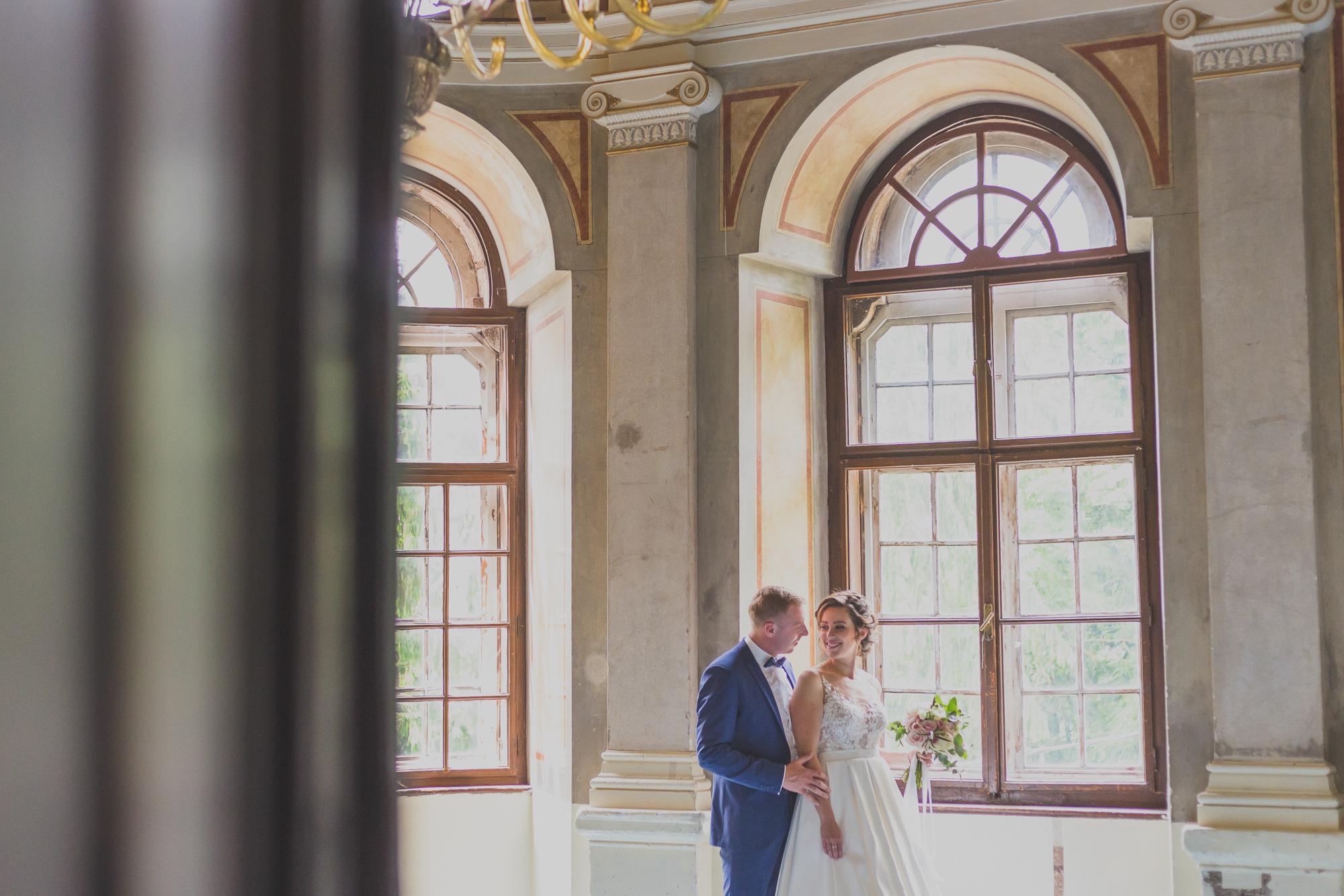 fotografie de nunta, miri la castel telki gornesti, cuplu in fata geamului, zambind, casdru larg cu interior castel