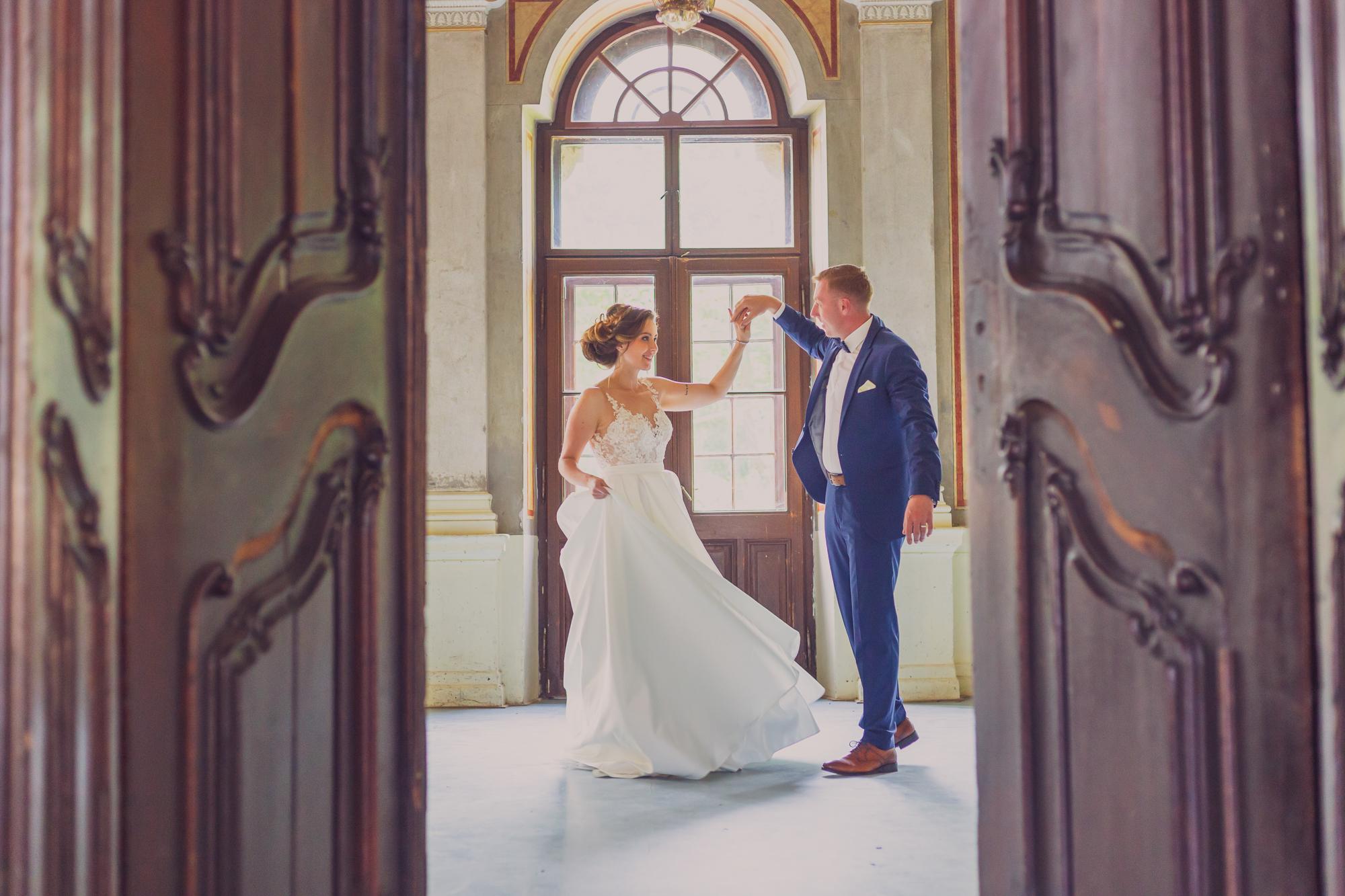 cadru larg cu cuplu care danseaza, fotografie de nunta, rochie de mireasa, costum de mire albastru, interior castel, castel teleki gornesti,
